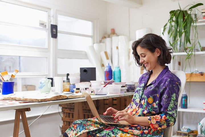 Young female artist smiles as she works on her laptop in her painters' studio
